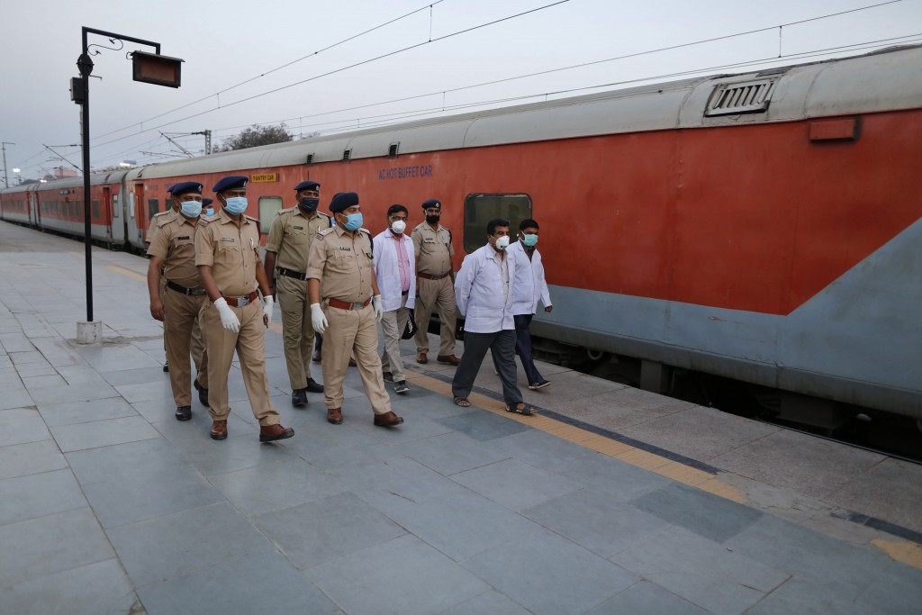 FILE- In this Tuesday, March 24, 2020, file photo, railway officials walk through a deserted railway station in Prayagraj, India. India's colossal pas...