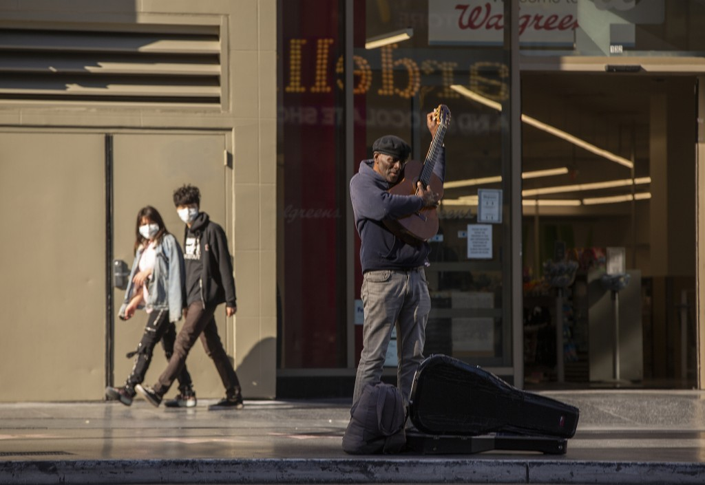 A lone street performer tunes his guitar on a mostly-empty Hollywood Boulevard in Los Angeles, Tuesday, March 24, 2020. New cases of the coronavirus s...