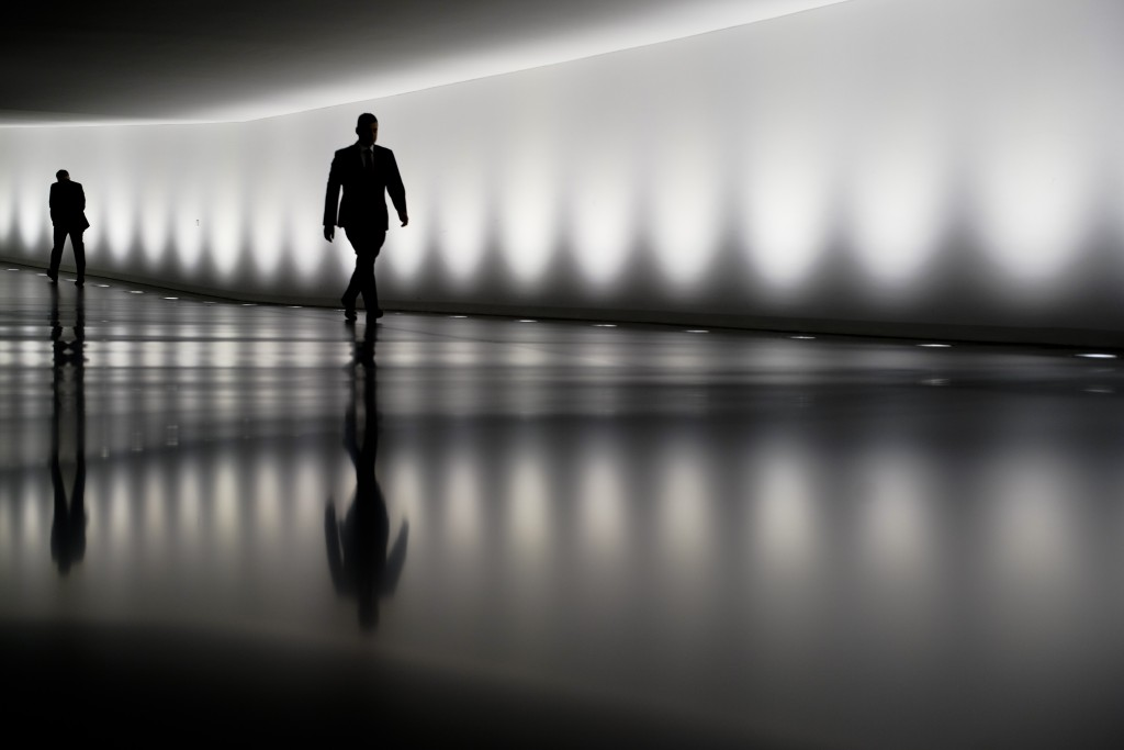 Two persons walk through a tunnel between the plenary hall and an office building of the German parliament Bundestag in Berlin, Germany, Wednesday, Ma...