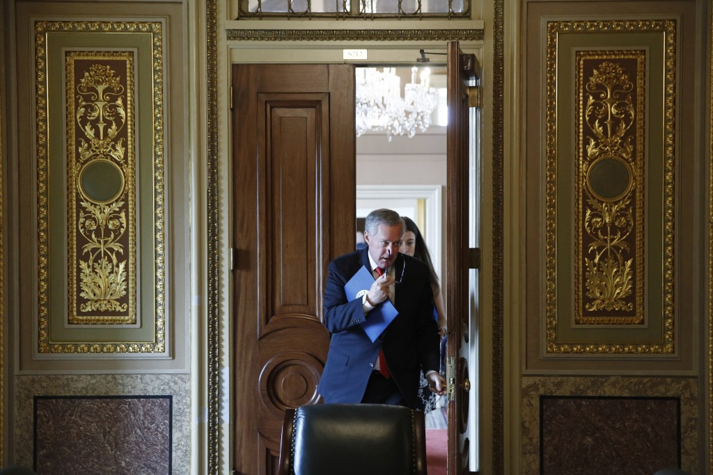 Acting White House chief of staff Mark Meadows departs a meeting on Capitol Hill in Washington, Tuesday, March 24, 2020, as the Senate works to pass a...