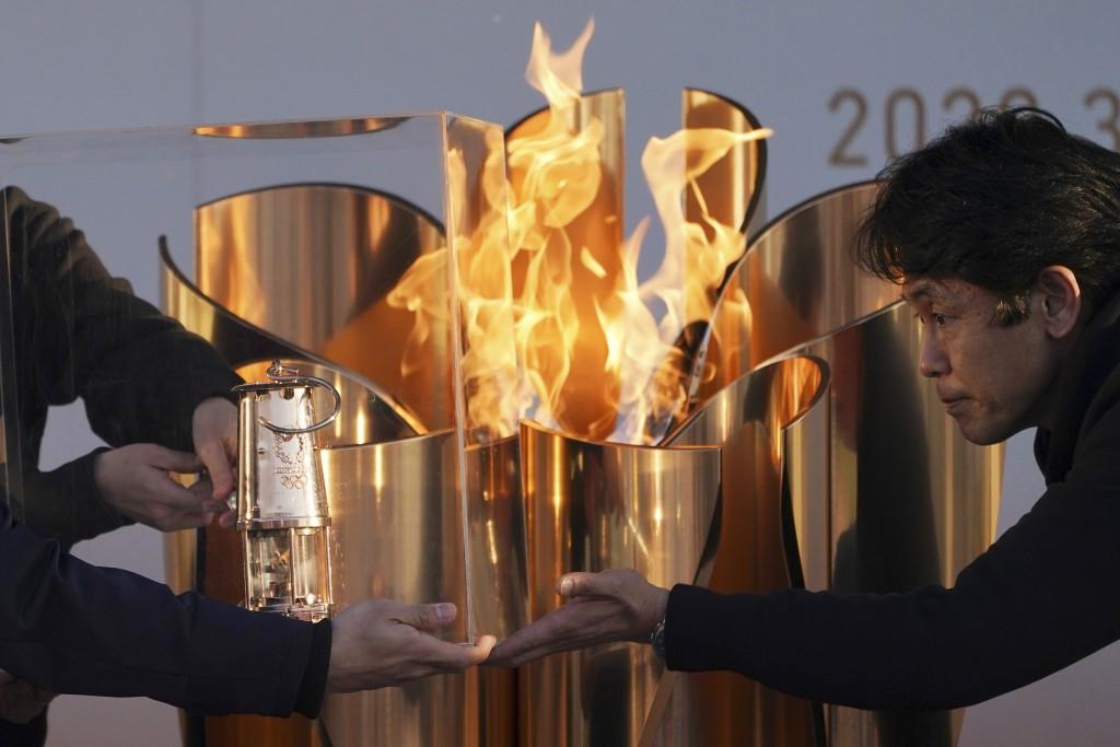 Officials light a lantern from the Olympic Flame at the end of a flame display ceremony in Iwaki, northern Japan, Wednesday, March 25, 2020. IOC Presi...