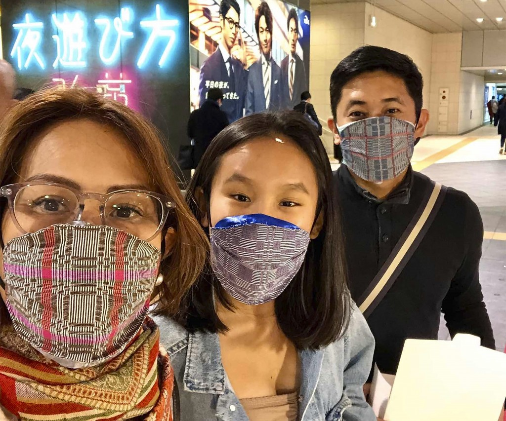 In this late February 2020, photo, Carlo Navarro poses behind wife Evie and daughter Gia for a family photo while wearing face masks during a trip to ...
