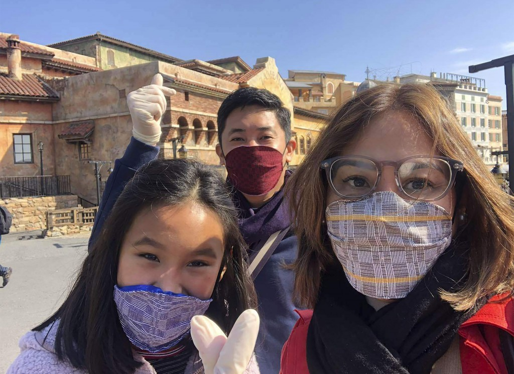 In this late February 2020, photo, Carlo Navarro poses behind his wife Evie and daughter Gia for a family photo while wearing face masks and gloves du...