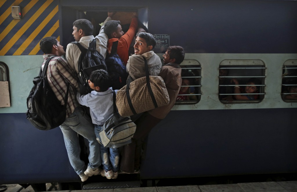 FILE - In this Friday, Nov. 16, 2012, file photo, Indians hang out from an overcrowded train to travel home for the Chhath Puja festival dedicated to ...