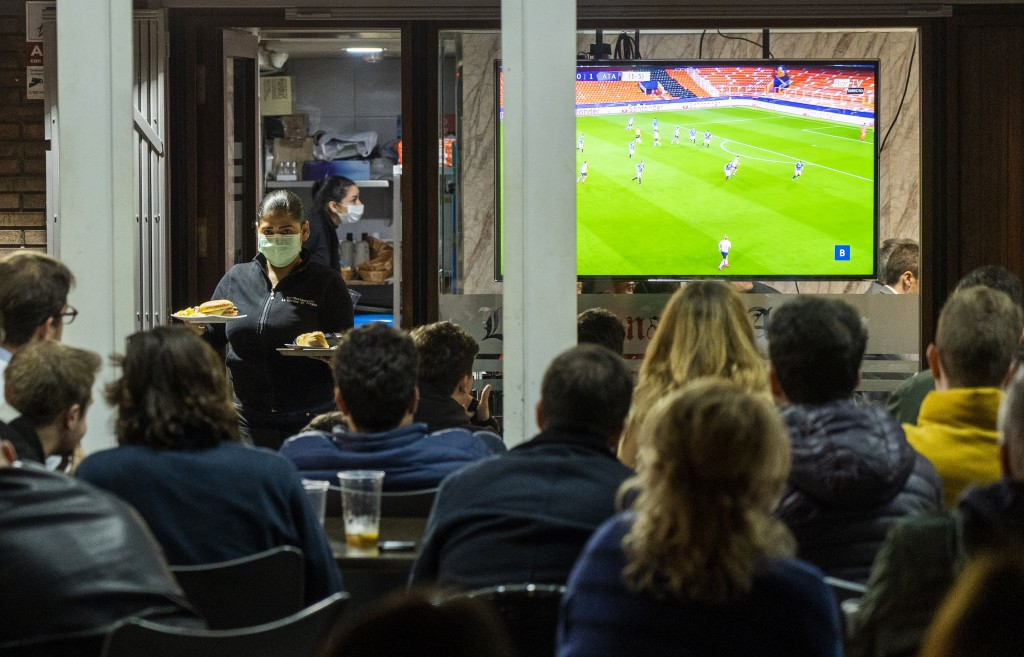FILE - In this Tuesday March 10, 2020 filer, waiters wearing masks serve food and drink in a terrace outside Mestalla stadium during the Champions Lea...