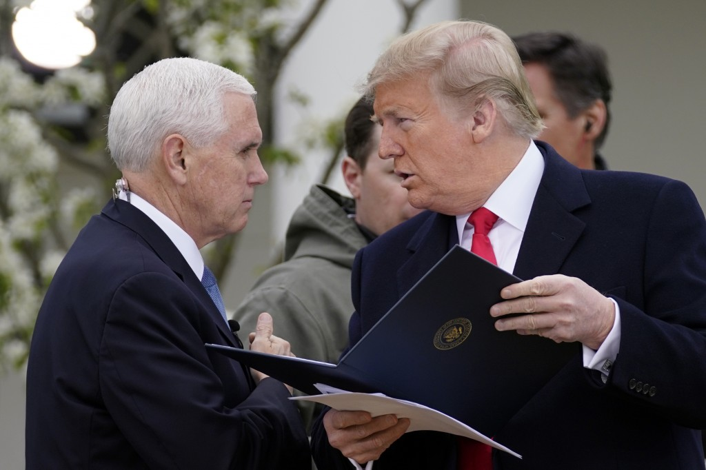 President Donald Trump speaks with Vice President Mike Pence as they arrive for a Fox News Channel virtual town hall, at the White House, Tuesday, Mar...