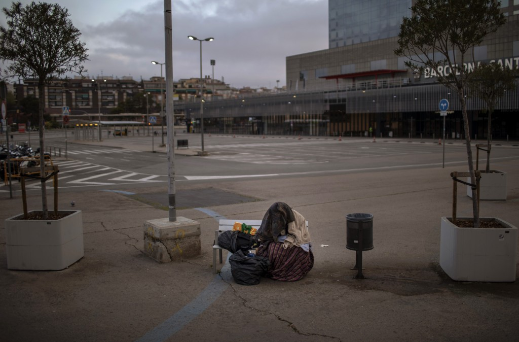 In this Sunday, March 22, 2020 photo, a man from sub-Saharan Africa covers himself with clothes and blankets as he sits on a bench at an empty car par...