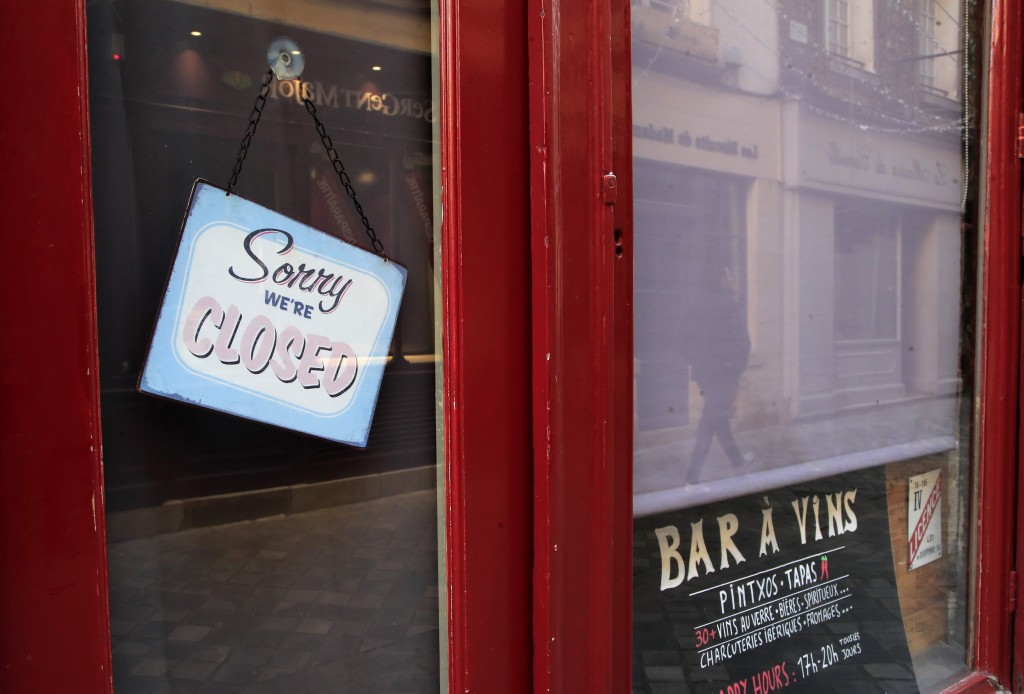 A sign hangs on the entrance door of a closed vin bar in Versailles, west of Paris, Tuesday, March 24, 2020. French President Emmanuel Macron urged em...