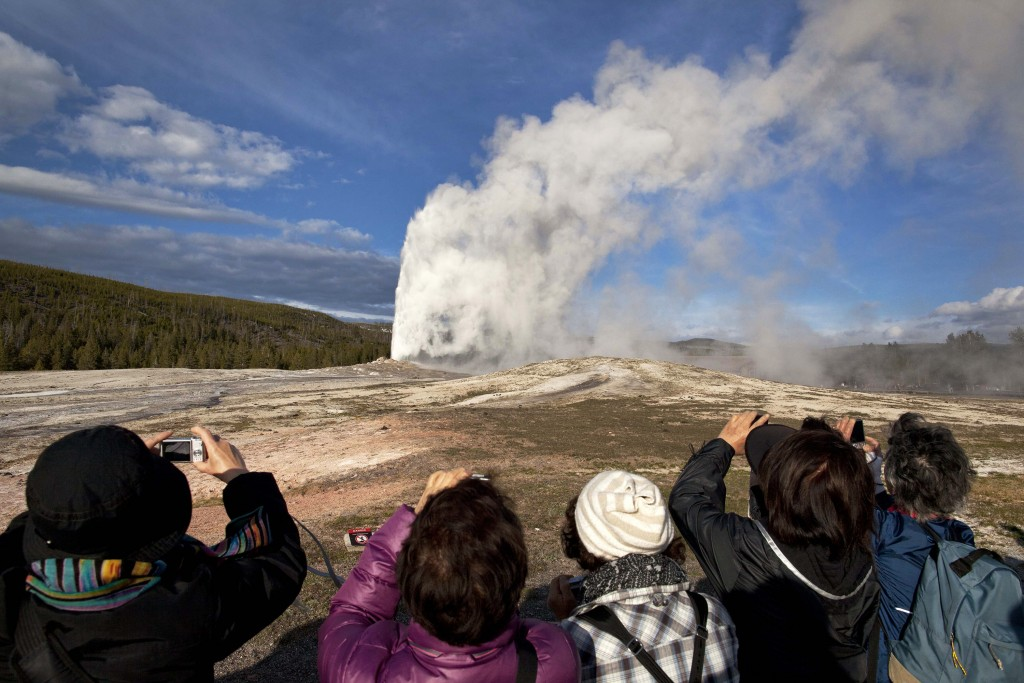 FILE - In this May 21, 2011 file photo, tourists photograph Old Faithful erupting on schedule late in the afternoon in Yellowstone National Park, Wyo....