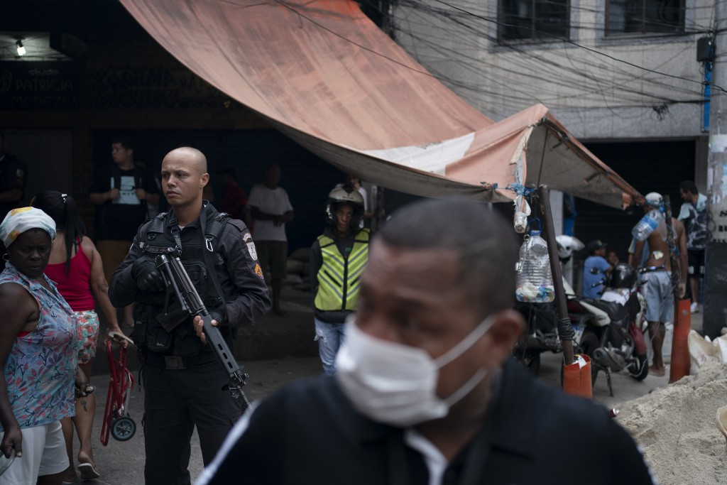 A police officer stands at the ready in a small market, as a local volunteer with a face mask walks away after distributing soap and detergent in an e...