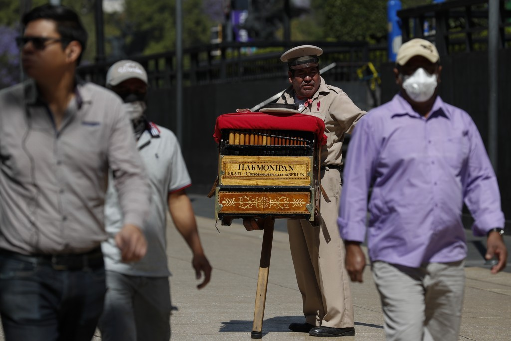 Organ grinder Moises Rosas solicits tips from pedestrians in central Mexico City, Tuesday, March 24, 2020. Rosas, who has been an organ grinder for 25...
