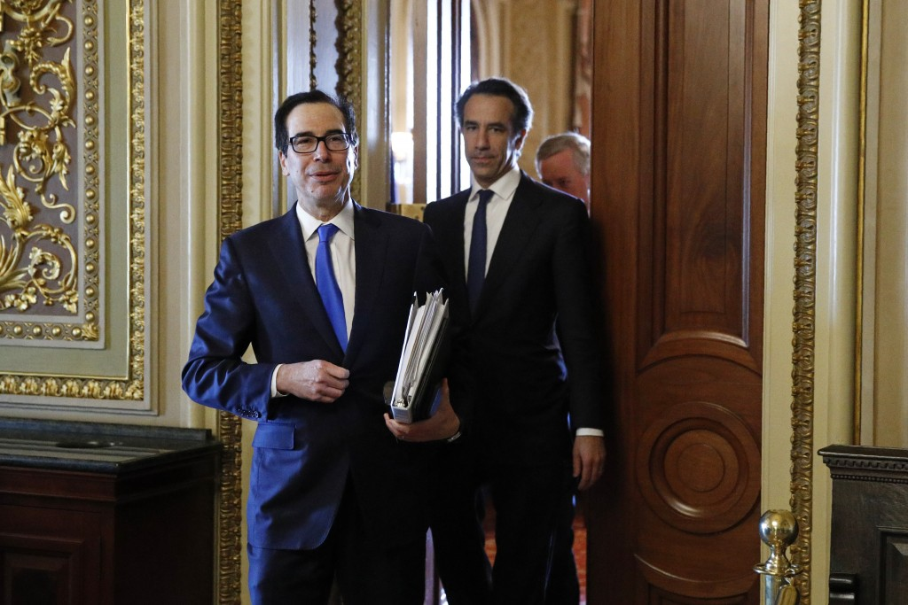 Treasury Secretary Steve Mnuchin steps out of a meeting on Capitol Hill in Washington, Tuesday, March 24, 2020, as the Senate works to pass a coronavi...