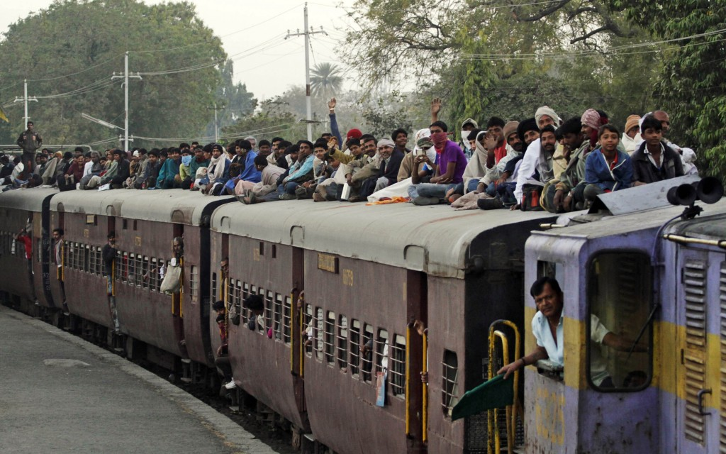 FILE - In this Tuesday, Feb. 21, 2012, file photo, Indian Hindu devotees sit on the roof of a train as they leave after attending Shivratri festival f...