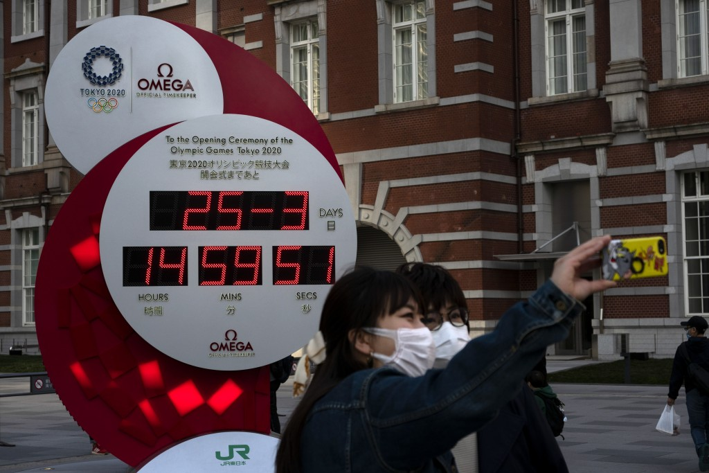 Two women take a selfie with a Tokyo 2020 countdown clock displaying the current date and time outside Tokyo Station, Wednesday, March 25, 2020, in To...