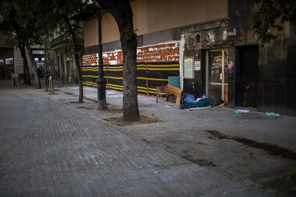 In this Thursday, March 19, 2020 photo, a man from sub-Saharan Africa sleeps in an empty street in downtown Barcelona, Spain. Authorities are scrambli...