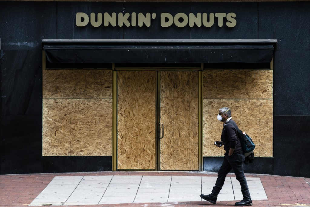 A person wearing protective masks due to coronavirus fears walks past a boarded up business in Philadelphia, Tuesday, March 24, 2020. (AP Photo/Matt R...