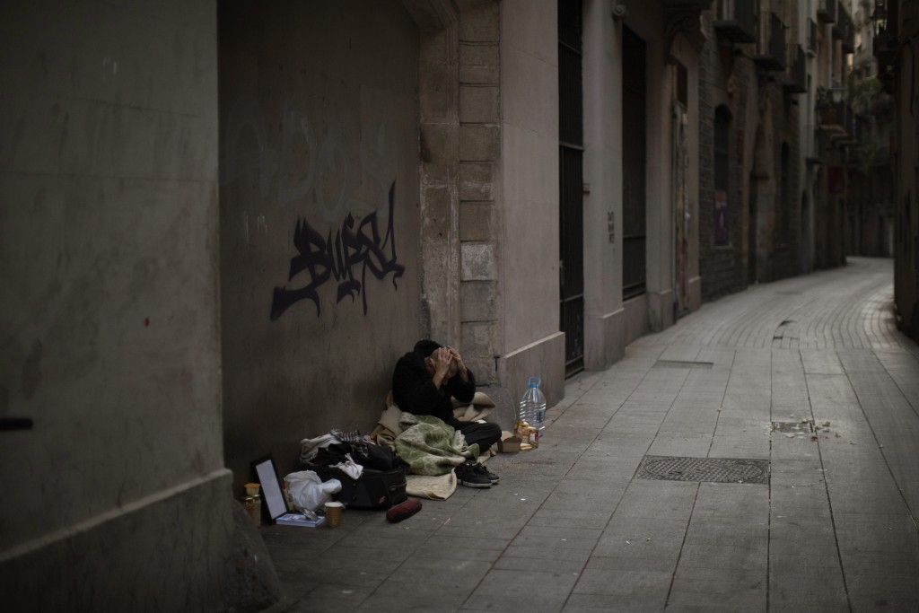 In this Saturday, March 21, 2020 photo, Javier Redondo, 40, covers his head with his hands as he waits for alms on an empty street in Barcelona, Spain...