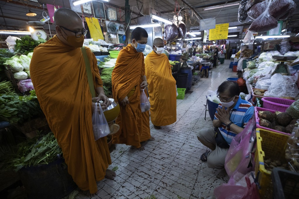A Thai Buddhist prays after offering food to Thai Buddhist monks as they wear face masks to protect themselves from a new coronavirus in Bangkok, Thai...