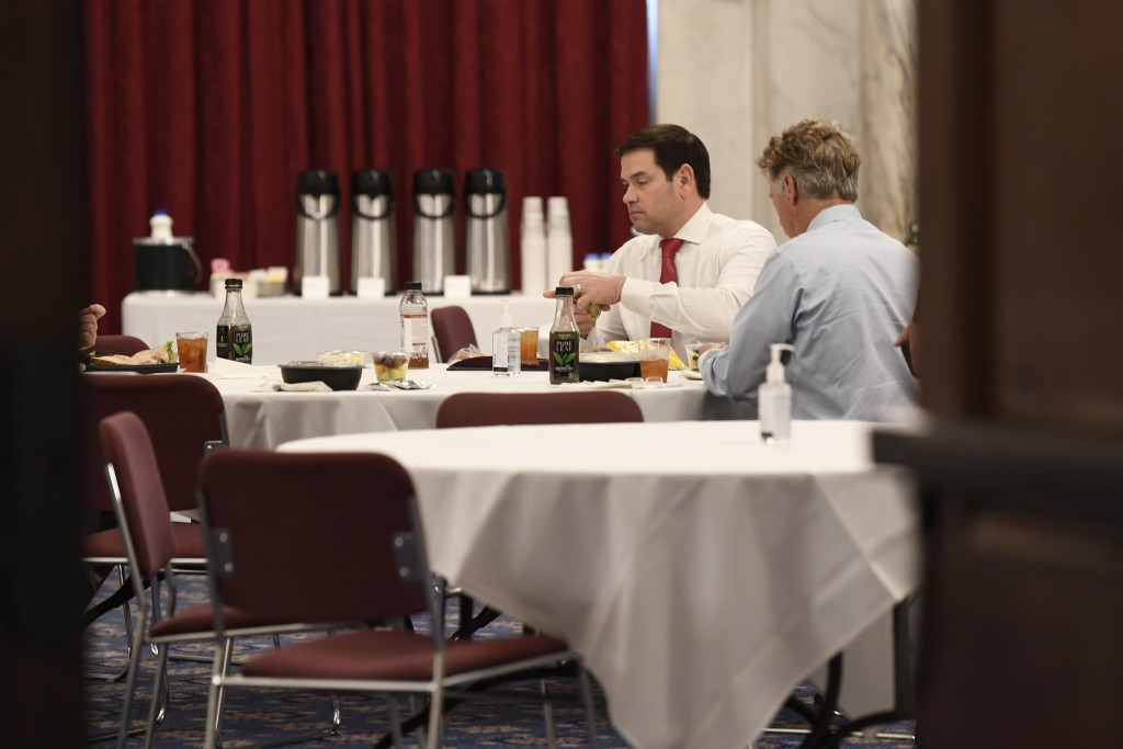 In this March 20, 2020, photo Sen. Rand Paul, R-Ky., right, Sen. Marco Rubio, R-Fla., left, have lunch at a Republican policy lunch on Capitol Hill in...