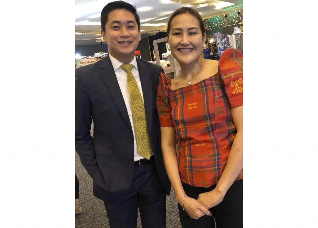 In this late February 2020, photo, Carlo Navarro poses with his wife Evie Navarro for a family photo during a trip to Tokyo. Days after he was cleared...