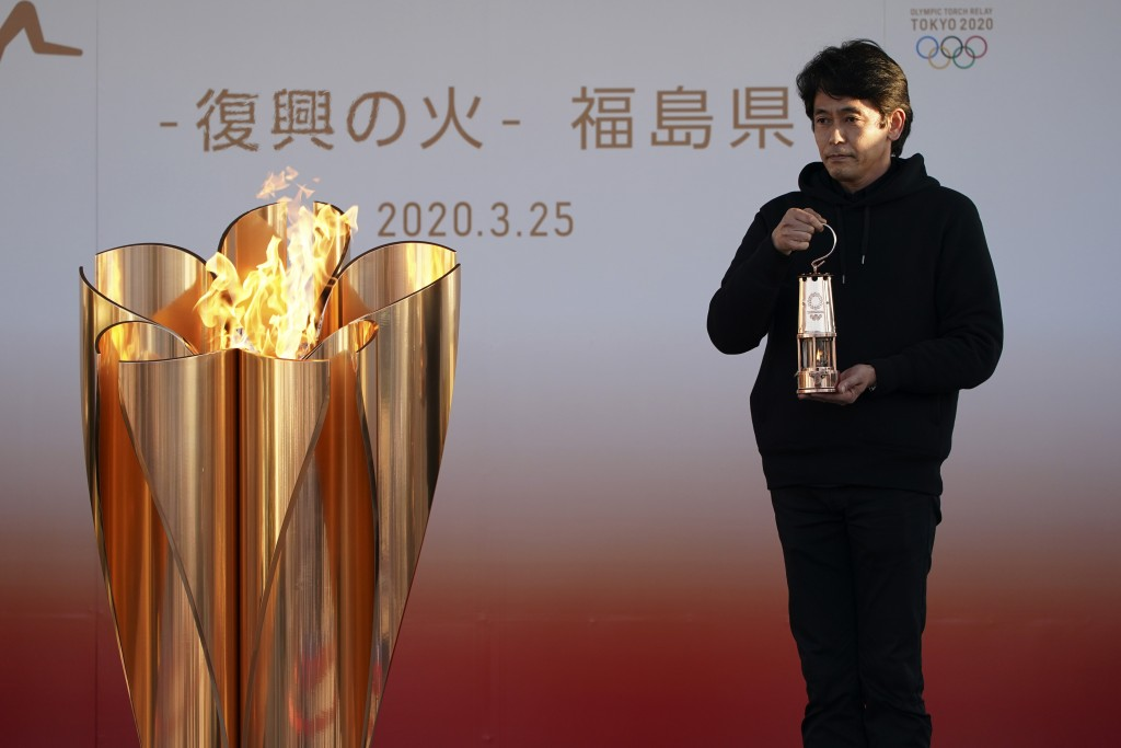 An official holds a lantern containing the Olympic Flame at the end of a flame display ceremony in Iwaki, northern Japan, Wednesday, March 25, 2020. I...