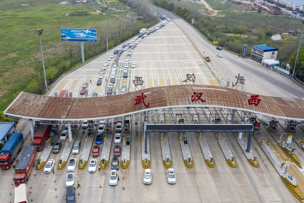 In this March 24, 2020, photo released by Xinhua News Agency, an aerial photo shows vehicles waiting to cross into Wuhan at a highway toll station in ...