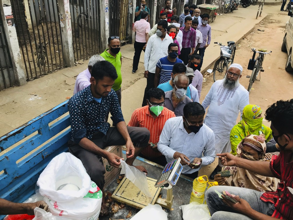 People line up to shop for essential items from a roadside truck Wednesday, March 25, 2020 in Dhaka, Bangladesh. The new coronavirus causes mild or mo...