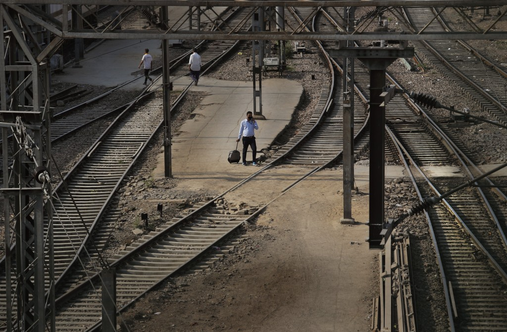 In this Monday, March 23, 2020, photo, a passenger walks past railway tracks at the deserted New Delhi Railway station during a lockdown amid concerns...