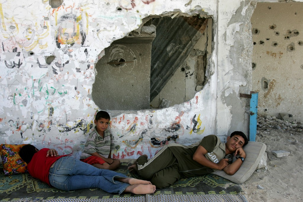 FILE - In this Aug. 10, 2005 file photo, Palestinians rest in the shade of a building destroyed during the Palestinian Intifada, on the outskirts of K...