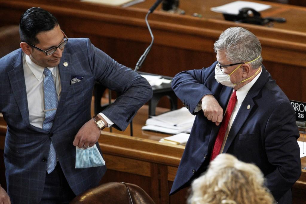 FILE - In this March 23, 2020, file photo Nebraska Senators Tony Vargas of Omaha, left, and Mark Kolterman of Seward, bump elbows at the State Capitol...