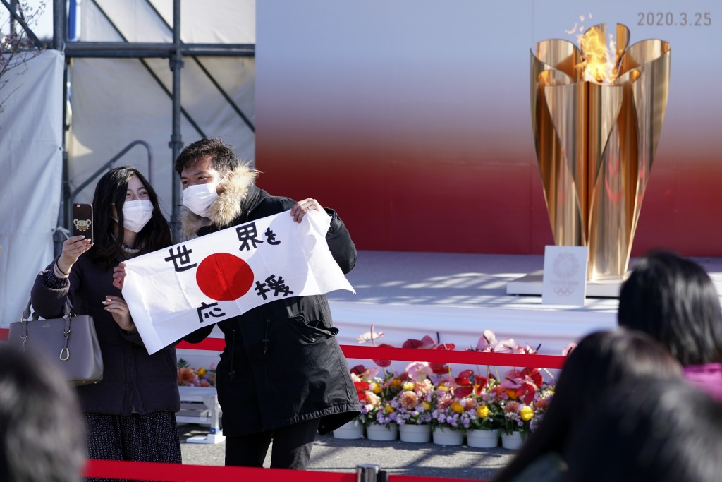 """Visitors pose with a national flag with characters reading """"Supporting the world"""" near the Olympic Flame during the Olympic """"Flame of Recovery"""" displa..."""