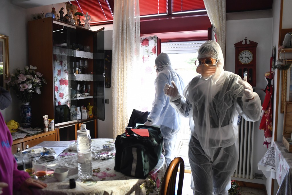 Medical staffers wearing protective gear, part of a special unit performing house calls, work in Bergamo, northern Italy, one of the areas worse-affec...