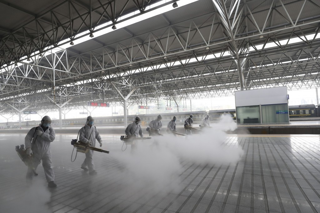In this March 24, 2020, photo released by Xinhua News Agency, firefighters conduct disinfection on the platform at Yichang East Railway Station in Yic...
