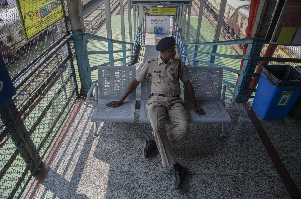An Indian railway police officer blocks a staircase at an empty railway station during lockdown in Gauhati, India, Wednesday, March 25, 2020. The worl...