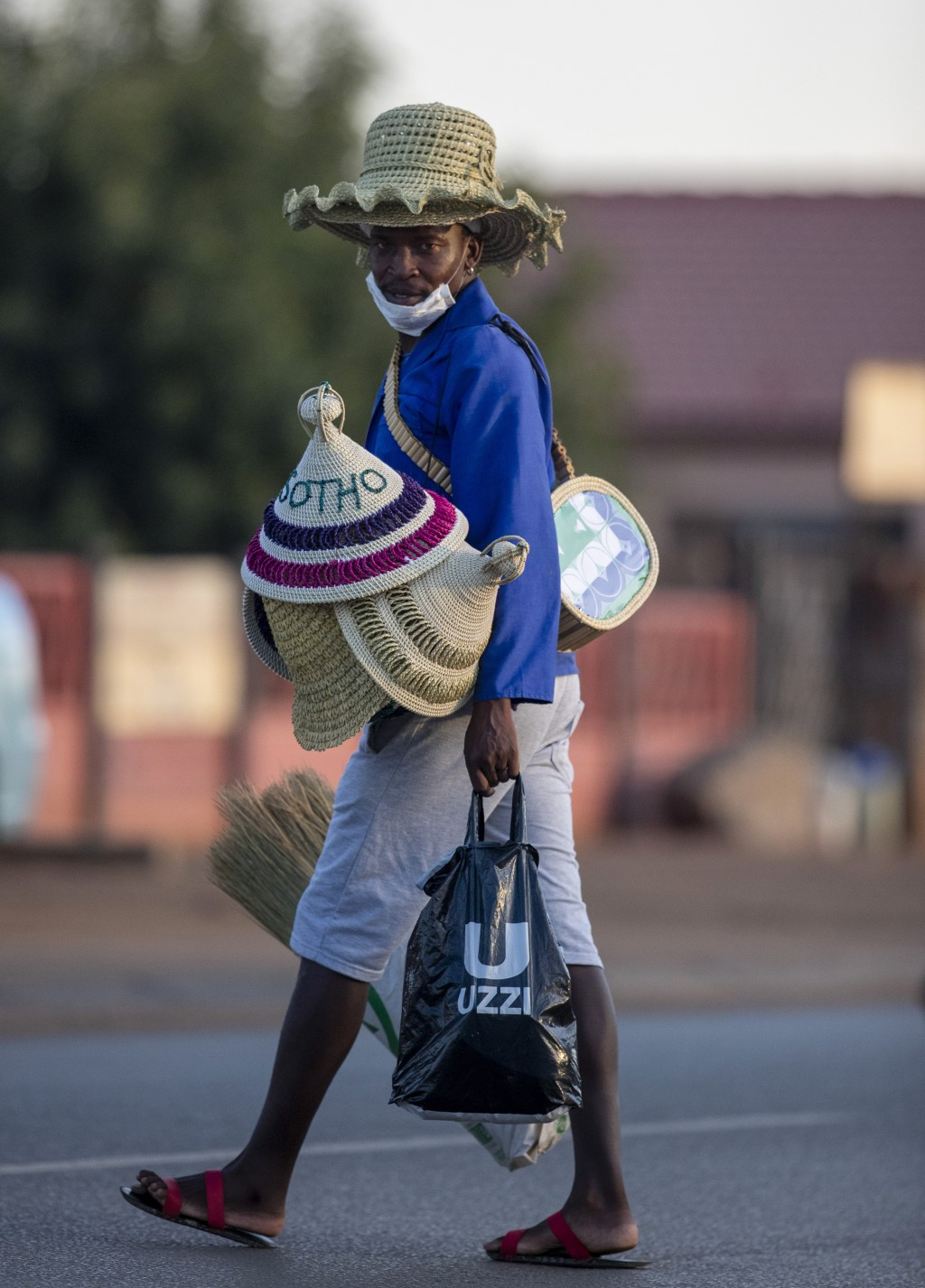A man wearing a mask, sells traditional hats on the street in Daveyton, east of Johannesburg, South Africa, Tuesday, March 24, 2020, a day after it wa...