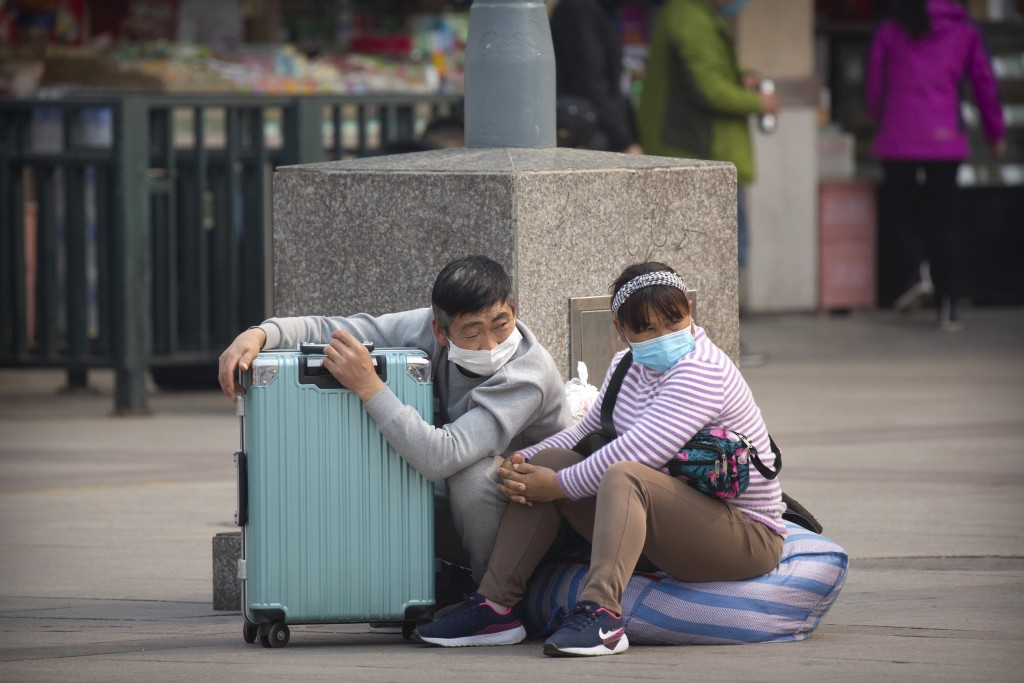 Travelers wearing face masks sit with their luggage outside the Beijing Railway Station in Beijing, Wednesday, March 25, 2020. Some train stations and...
