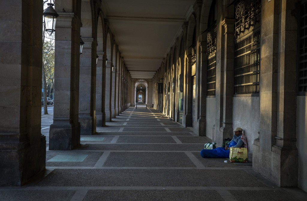 """In this Friday, March 20, 2020 photo, Riccardo, 32, sits in empty arcades in downtown Barcelona, Spain. """"I thought I had seen everything during all th..."""