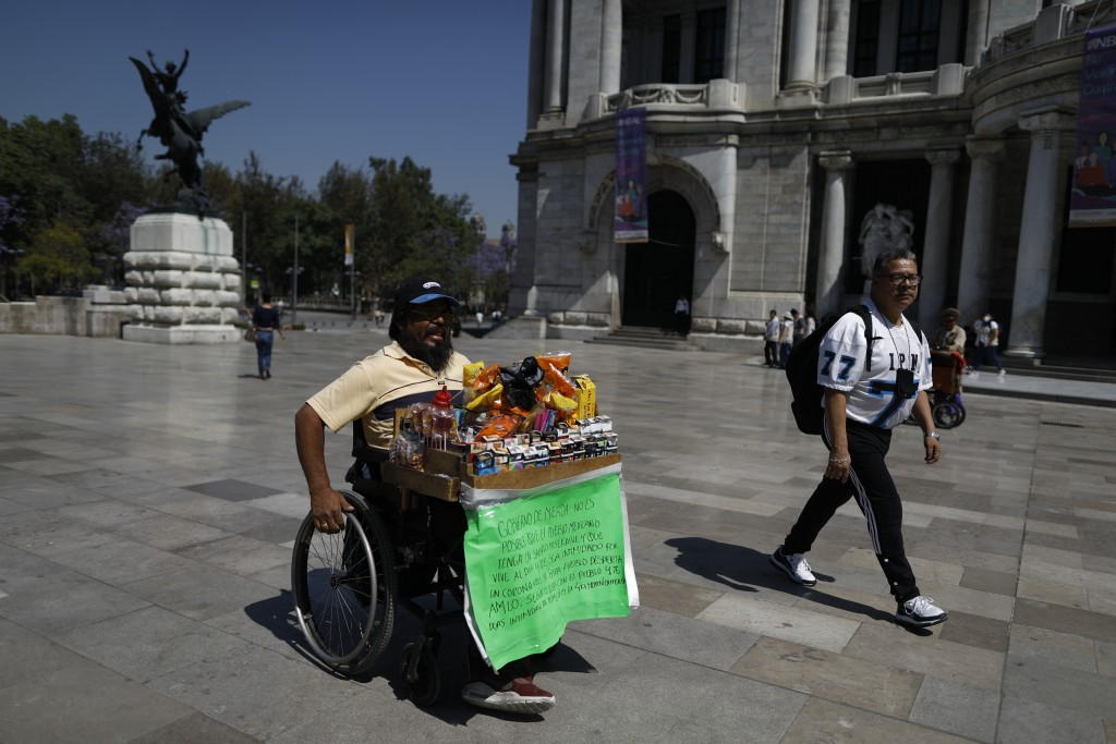 Guillermo Gonzalez Sanchez sells cigarettes and snacks from atop his wheelchair, outside the Palace of Fine Arts in downtown Mexico City, Tuesday, Mar...