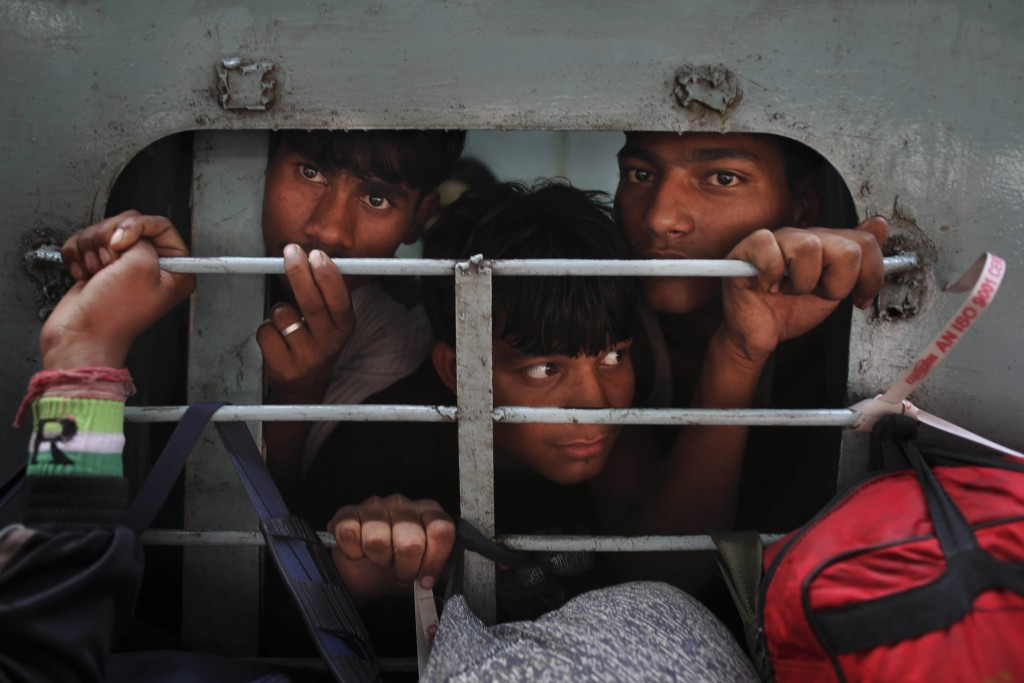 FILE - In this Nov. 16, 2012, file photo, Indians look out from an overcrowded train to travel home for the Chhath Puja festival dedicated to the Sun ...