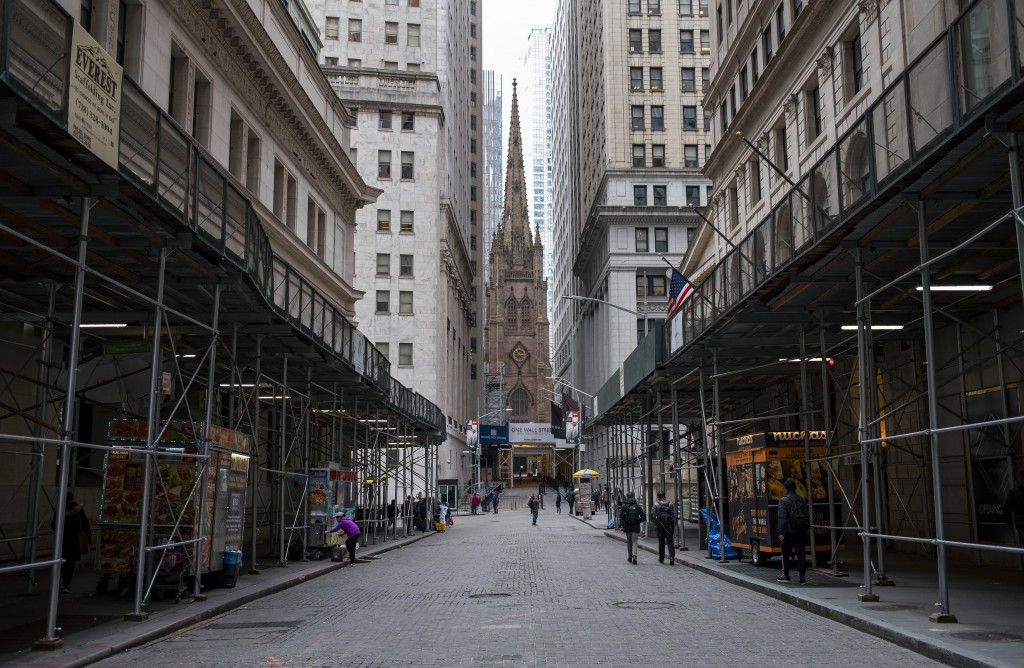 FILE - In this Monday, March 16, 2020, file photo, pedestrian traffic is light along Wall Street in Lower Manhattan in New York. The banking system is...