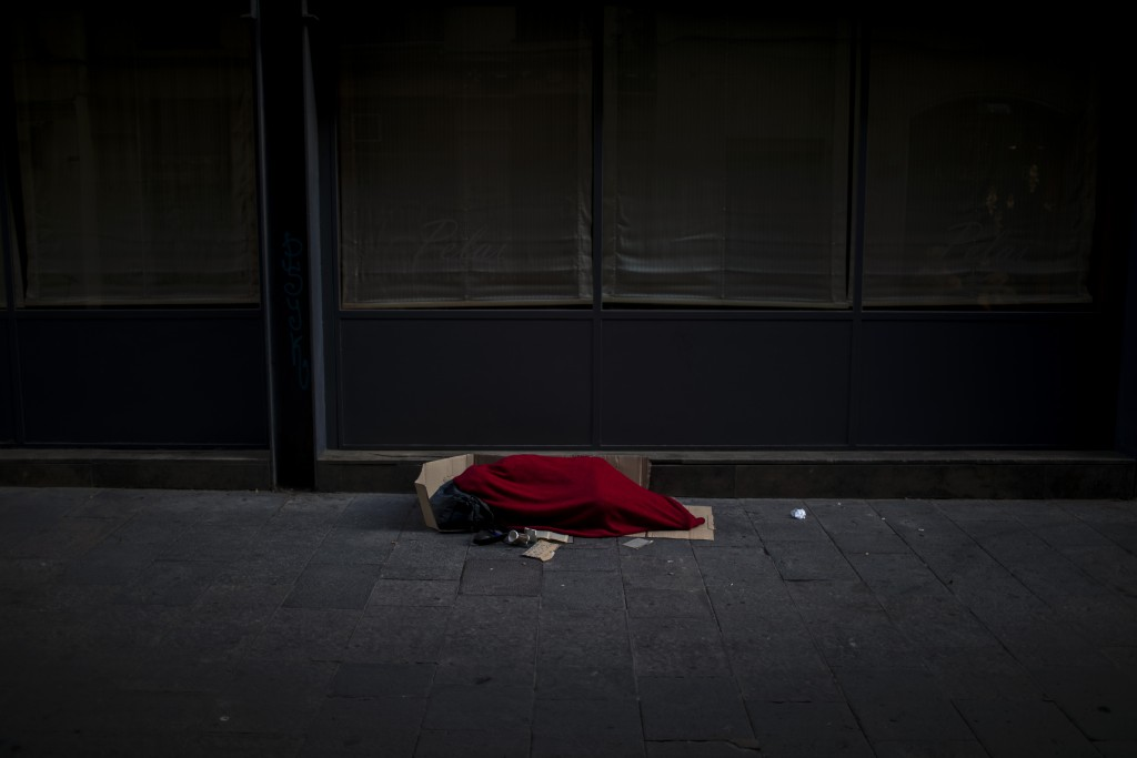 In this Sunday, March 22, 2020 photo, a man covered with a blanket sleeps in an empty street in Barcelona, Spain. In Barcelona sleeping figures with b...