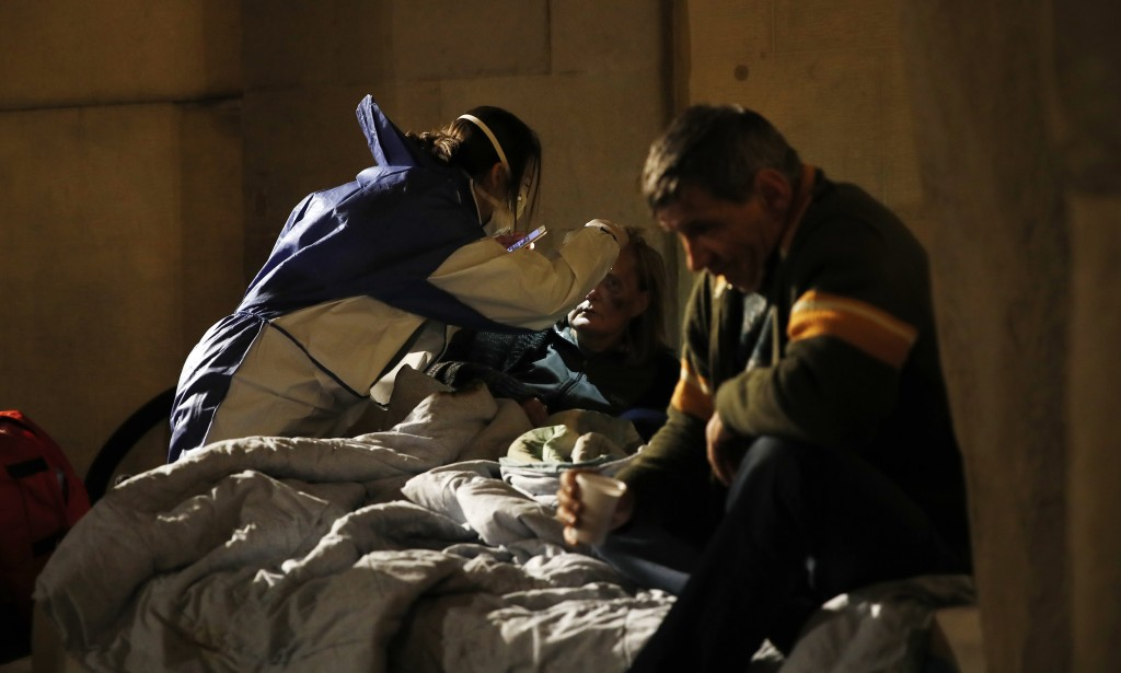 A volunteer nurse wearing a mask tends to an homeless in Milan, early Wednesday, March 25, 2020. The new coronavirus causes mild or moderate symptoms ...