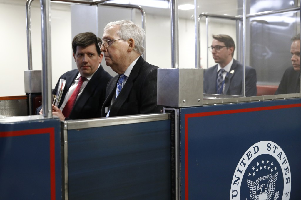 In this March 18, 2020, photo Senate Majority Leader Mitch McConnell of Ky., rides a subway car on Capitol Hill in Washington before a vote on a coron...