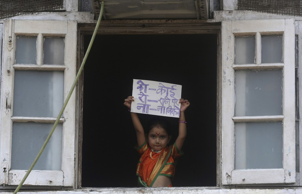 """A girl dressed in traditional attire to celebrate """"Gudi Padwa"""", or the Marathi New Year, stands by a window and holds a placard with an acronym for th..."""