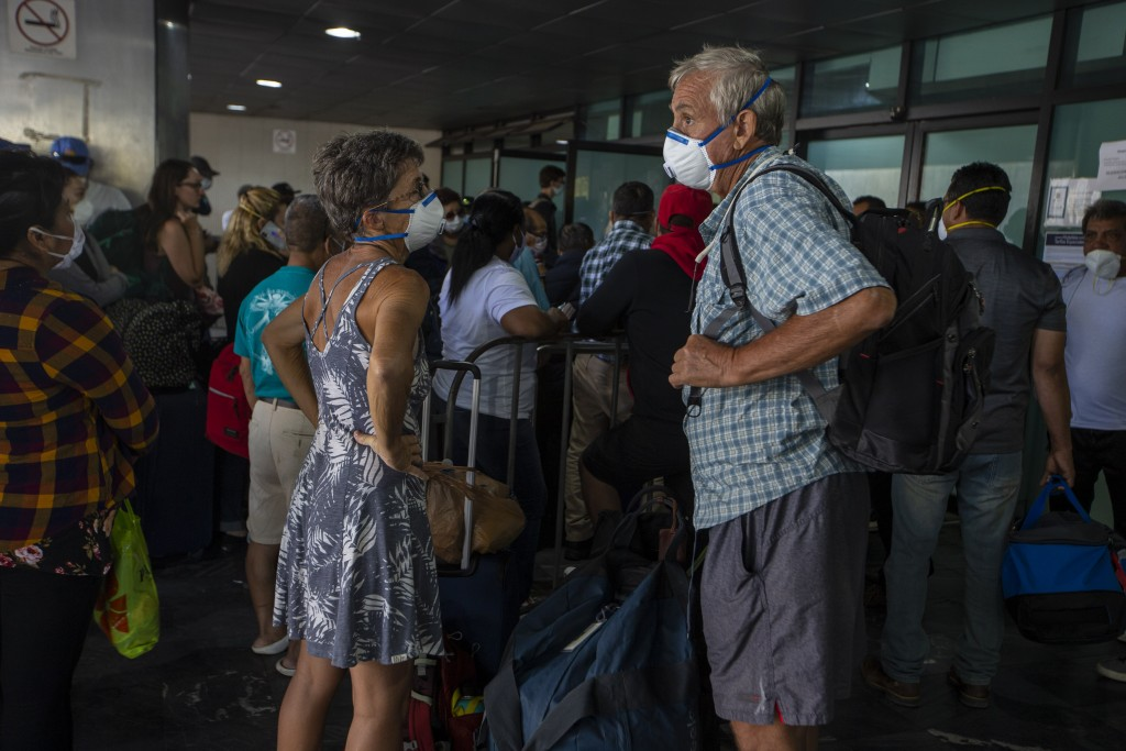Travelers wait for a charter flight coordinated by the U.S. embassy at the La Aurora airport in Guatemala City, Tuesday, March 24, 2020. American citi...