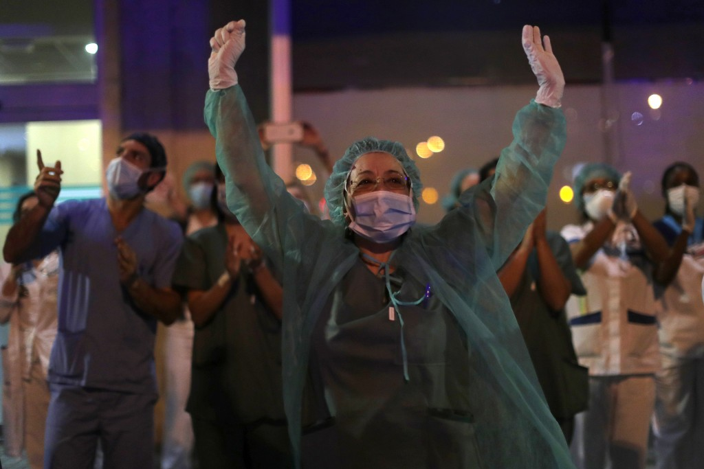 FILE, In this Saturday, March 21, 2020 file photo, health workers react as people applaud from their houses in support of the medical staff that are w...