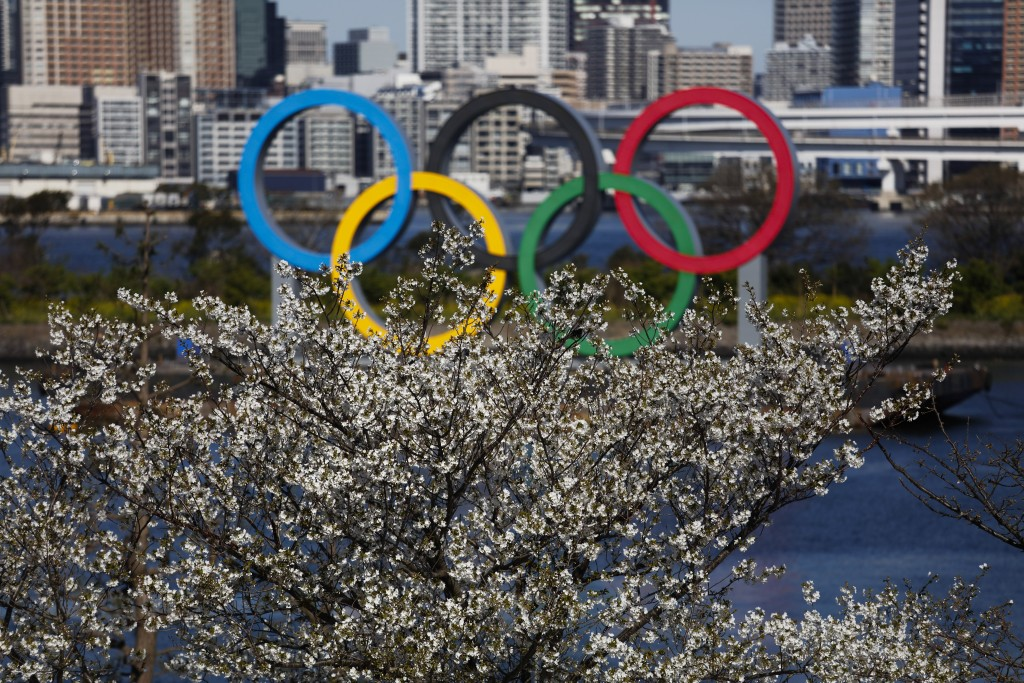 The Olympic rings floating on a barge are seen behind cherry blossoms Wednesday, March 25, 2020, in the Odaiba section of Tokyo. Not even the Summer O...