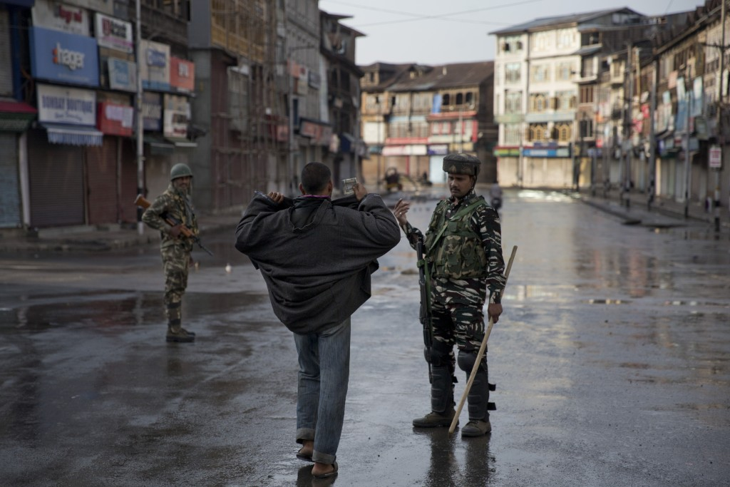 In this Aug. 8, 2019 file photo, an Indian paramilitary soldier orders a Kashmiri to lift his robe before frisking him during curfew in Srinagar, Indi...