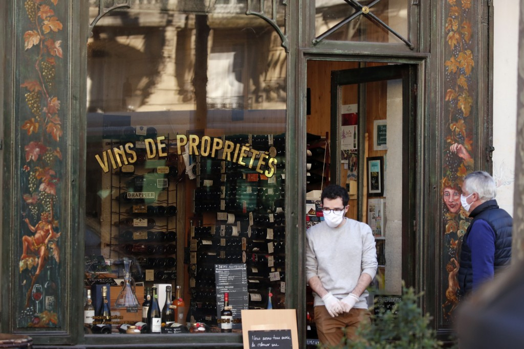 Parisian wearing protective masks stand in front of a wine shop in Paris, Tuesday, March 24, 2020. French President Emmanuel Macron urged employees to...