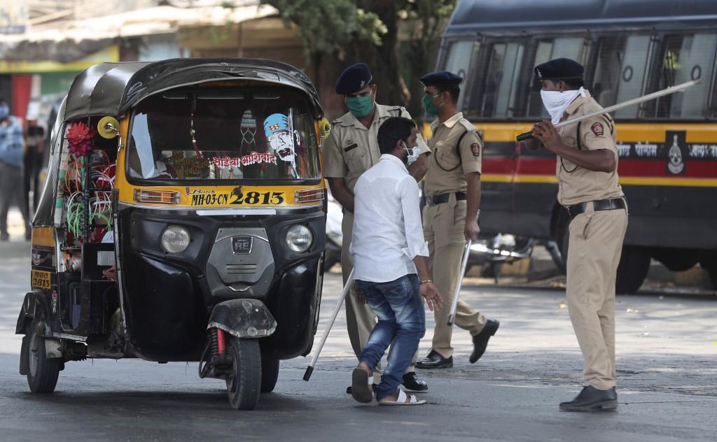 Policemen beat a curfew violator in Mumbai, India, Wednesday, March 25, 2020. The world's largest democracy went under the world's biggest lockdown We...